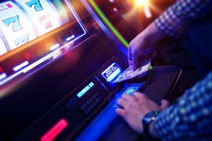 Mann spielt mit Geld am Spielautomat mit Trick